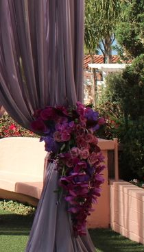 Two large clusters of purple hydrangeas, purple foliages, fuchsia purple phalaenopsis orchids, orange pincushions, purple tulips, and plum amaranthus will accent the top corners of the chuppah.