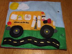 Wheels on the Bus Quiet Book Page - The bus wheels rotate on brads. The bus door opens with velcro. There is a small button tethered to go into a black money box at the top of the stairs. There are 2 passengers. Both passengers are movable from one seat to another with velcro attachments. There is a non-working horn on the bus as this is a quiet book after all. There is a windshield wiper that is movable. This is made from a clipped zip tie pilfered from the hub's garage.
