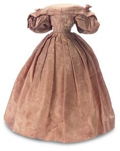Of a very fine rose patterned silk faille,the cut of the petite gown is low on the shoulders,yet with a modestly cut V-shaped bodice with dart- shaped snug fit and having piping at the darts and waist. The very wide collar is triple-pleated and extends in points over the very full lantern sleeves with tulle ruffle at the bands. The skirt is pleated all around,meeting at the center front. Some fraility to silk. Circa 1840.