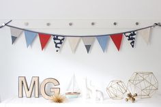 A nautical themed bunting banner that will add a little splash to your nursery walls or a baby shower table. The garland consists of (10) flags alternating in stripes, red, baby blue, and a whale print. • • • • • • • • Please allow 3-5 days for shipping. • • • • • • • •  PRODUCT DETAILS • (10) 7 in. Flags • Length: Approx 5 Ft. • Materials: Cotton + Linen Fabrics. • Cleaning Instructions: Spot Clean Only. Low Iron OK.  PLEASE NOTE • Colors may vary slightly from screen. • NOT a toy | Decor…