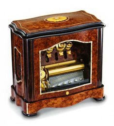 This lovely and hard to find Music Box by Reuge of Switzerland in Burr Vavona is just beautiful. It has mother-of-pearl lining and rosetta inlay. It is a less common vertical piece with the traditional 3 song 72 note movement. The three included songs are by Tchaikovsky and include: March of the Toy Soldiers, Waltz of the Flowers, and Dance of the Sugar Plum Fairy.