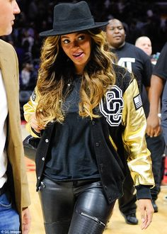 Casual chic: The Drunk In Love singer looked stylish in a black and gold varsity jacket over a black top as she showed no signs of a baby bump