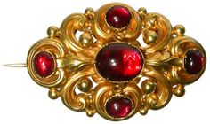 A Victorian repoussé gold cabachon garnet brooch of pierced oval form with foliate and scroll work decoration, original locket back, 1.75in wide.