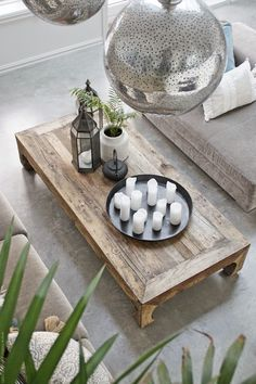 love this low, large coffee table topped with candles, lanterns and plants for…