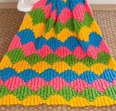 A carnival of colors – in simple single crochet!  This baby blanket consisted of 17 Levels, each crocheted with one color at-a-time. Each Level was worked vertically in rows of corrugated single crochet and joined to the previous Level as you work, with strategic increasing and decreasing producing the shell-like pattern.  The main pattern was a 12-row repeat; although, it took three or four Levels before I fully memorized it. Then it was smooth sailing! Best of all: Once the final Level was…