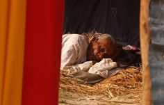 An Indian pilgrim rests on a bed of hay on a sunny day following last week's cold spell across the region, ahead of the Kumbh Mela in Allahabad, on January 9, 2013. (Sanjay Kanojia/AFP/Getty Images)