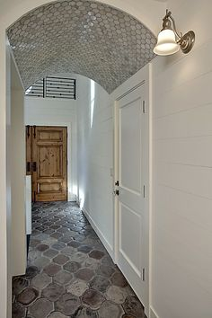 Unique hallway design with a rustic door, stone tiled floor and shimmery tile arched ceiling.  From a 4-story Craftsman style home construction by Lavallee Construction, discovered on Porch.com