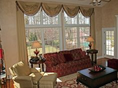 A palette of two rich colors – gold and burgundy – create an elegant formal living room. Upholstered furniture, heavy end tables and gold drapes with a scalloped valance polish off the look.