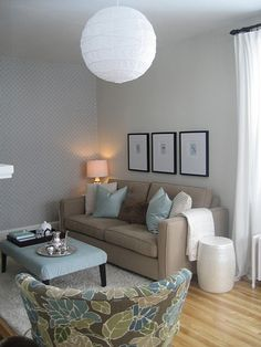 Beige couch light grey walls with white and blue pillows.