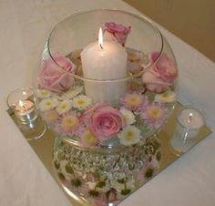 Centro de mesa con flores velas y agua