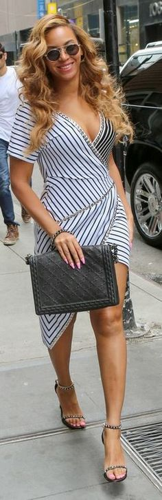Who made Beyonce Knowles' round sunglasses, black studded sandals, and white stripe sequin dress?