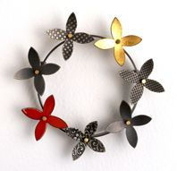 round kinetic flower brooch with red enamel and gold leaf
