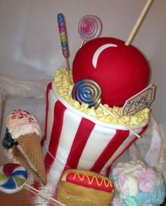 Carnival Cake!  Had a blast making this cake!  Everything you see is edible (accept the sticks) I made every kernal of popcorn out of fondant!  The ice cream cone is actually a cupcake!  I think this cake came out really well.  www.heavenlysweetsbakery.com