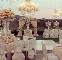 Lustre, roses blanches et juponage blanc des chaises pour un dîner en extérieur élégant