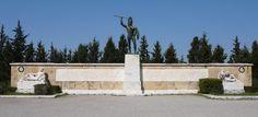 """Monumento de 1955 em homenagem aos 300 de Esparta, no centro uma estátua do Rei Leônidas, em sua base a inscrição: ΜΟΛΩΝ ΛΑΒΕ que significa """"Venham pegá-las"""", que teria sido a resposta do rei espartano aos Persas quando esses falaram para se renderem e entregarem suas armas."""