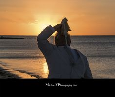 "Key West's ""Conch Republic Minister of Love"" blows from his custom conch shell horn following a sunrise beach wedding."