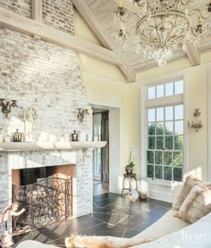 A crystal chandelier brings a touch of elegance to the solarium, which was designed as a retreat for homeowner Angela Kroeger. The fireplace is part of the same whitewashed brick massing used in the kitchen, and the fireplace screen features more of the ornate ironwork the owners love.