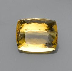 Golden Beryl, var. Heliodor Brazil A rich golden beryl of excellent saturation, this gemstone is exemplary for its transparency, luster and fine faceting of the cushion-shape. Weighing approximately 40.5 carats and measuring 22.0 x 19.0 x 12.5mm