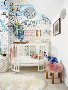a sweet colorful nursery with hand-drawn wallpaper