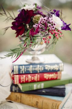 Floral centerpiece on books | Bellamint Photography and Sunflower Creative | see more on: http://burnettsboards.com/2014/09/literary-wedding-book-page-wedding-dress/