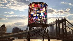 The Brooklyn skyline welcomes a colorful new addition this summer with the installation of Watertower by artist Tom Fruin. The sculpture, measuring 25' by 10', was created using 1000 pieces of salvaged plexiglass welded together to form the vibrantly colored piece. Land Art, Brooklyn Bridge Park, Brooklyn Nyc, Brooklyn Dumbo, Nyc Skyline, Hello Brooklyn, Manhattan Skyline, Street Art, Glass Art