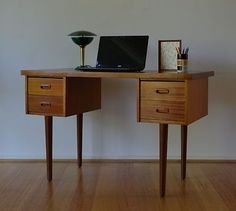 Retro mid century danish modern teak four drawer desk. Love how light it is with the tall legs. It would work in a living space as well.