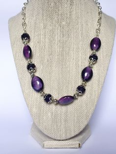 Dark purple glass beaded necklace, antiqued silver spacer beads and silver metallic beads in between. The crystals are flanked by two fancy silver bead caps. A silver chain and a clasp complement this