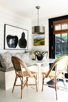 A built-in corner banquette in a small kitchen + Art in the kitchen by Lizzy Love and the Apple Pear Poster from Enzo Mari #artinthekitchen #art #abstractlandscape #rivierachairs #serenaandlily #shiplap #builtinbanquette #kitchennook #eatinkitchen #saarinen