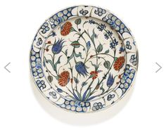 An Iznik polychrome pottery dish with floral stems, Turkey, circa 1580, decorated in underglaze cobalt blue, viridian green and relief red with black outlines, with a leafy tuft issuing floral sprays, including three large carnations, tulips, hyacinths and prunus branches, the rim with breaking wave pattern, floral details to exterior, old collection label to underside and single red bole dot in the centre 31cm. diam.