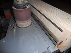 """Planer Knife Sharpening Jig by SASmith -- Homemade planer knife sharpening jig constructed from layers of glued and clamped plywood. Knives are secured in 1/8"""" slots and run past progressively finer grades of grinding belts, from 40-320 grit. http://www.homemadetools.net/homemade-planer-knife-sharpening-jig"""