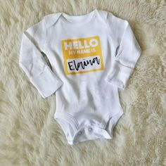 Our unisex baby personalized Hello My Name Is infant newborn bodysuit features the baby boy or girl name of your choosing in your choice of color and font and is the perfect fresh 48 hospital photo outfit, baby coming home outfit, first photo outfit, and a super unique baby shower gift for baby