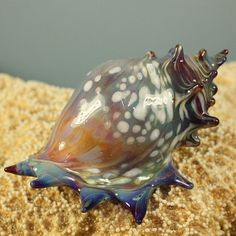 This is a a beautiful seashell. This seashell is made from durable borosilicate glass and has a beautiful shading of pale amber, gray, blue, green,