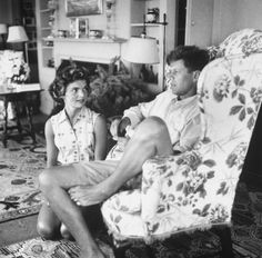 Socialite/photographer Jacqueline Bouvier kneeling on floor, listening adoringly to shorts-clad fiance Sen. John Kennedy as he chats w. unseen sibling in living room at the Kennedy family summer house.
