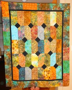batik quilt made with layer cakes and navy blue fabric.