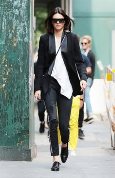 Kendall Jenner wears a Victoria Beckham Asymmetric Draped Tank with a Blk Dnm Jacket and Etienne Marcel jeans. She accessorizes with a Saint Laurent Monogramme Bourse Mini Leather Bucket Bag.