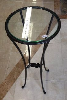 """Small iron stand or table with a love knot detail and glass top. Equally beautiful for holding a plant or your glass of wine. 12"""" diameter, 28"""" tall."""