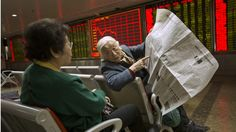 Chinese stock investors look over a newspaper in a brokerage house in Beijing. Photo: AP