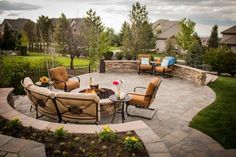 This terraced stone patio features multiple entertainment levels. One area features a lovely fountain, while another includes a seating area with fire pit. A curved stacked-stone wall provides additional seating when needed.