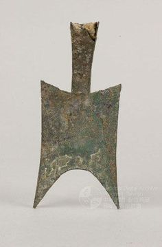 Bu (spade-shaped with pointed feet bronze currency).  This blank Bu coin with its high shoulders, hollow head and pointy foot is from the East Zhou dynasty.   The Bu Currency was very popular in the Sanjin region. It was the earliest style of metal currency, and the blank Bu currency is the ancestor of the Bu currency system. Later on, the Bu currency became smaller, the hollow head became a flat head and the pointy foott became square or rou.