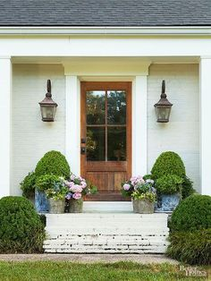 Love the symmetry of this tiny front porch, the over-sized window on the door and the lanterns!