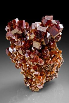 VANA09-28  Vanadinite Mibladen, Morocco   9 x 7 x 7 cm  Rising up from a triangular-shaped natural pedestal of matrix is a huge, statuesque, mound of intergrown, brick-reddish vanadinite crystals to 1.7 cm across. This assemblage of robust barrel-shaped crystals exhibits fairly uniform dark brick-red color and moderate if not highest luster, although the front-facing faces are more lustrous than side faces. Rarely do you see so much pristine, large, crystallized vanadinites piled up in one…