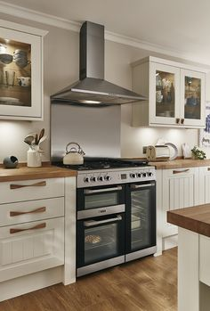 A beautiful traditional looking cooking area. A classic look with wooden worktop and handles. The Burford Tongue and Groove Shaker style kitchen from Howdens, here shown in Ivory.