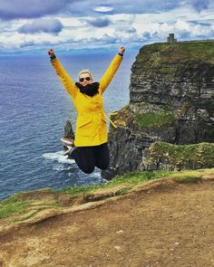 Jumping for joy on the Cliffs of Moher.  What a cute yellow belted jacket that looks so bright against this background!  Photo from @ erinbrown_likethecolor