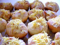 Ensaymada--Sweet Brioche; Sweet butter bread. Special fillings include Ham, Macapuno, and Ube. It is topped with melted butter and grated cheese and sugar after baking.
