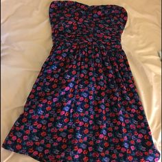 Cute navy blue & red floral print strapless dress Adorable strapless dress in dark blue with blue red & green floral print. Strapless with interior elastic to prevent slipping. Shirring under bustling. Mini to knee length depending on your height. Fully lined in blue. Interior fabric flaw pictured: fraying of fabric inside. Should not detract from dress. Dress looks like new on. Dresses Strapless