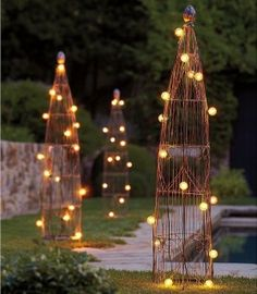 Fun, structural, lighting feature for the garden.  Can I make these with large tomato cages wrapped with grapevine and patio lights or twinkle lights?  This group of 3 is nice.