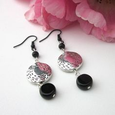 These earrings consist of etched silver pewter coin shaped beads, round black glass and round flat black coin beads.  They dangle from black coated copper earring wires. These cute earrings are one of