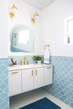 Interior designer Emily Henderson gave her home's outdated bathroom a fresh new look thanks to shiny gold fixtures, light blue wall tiles and a coat of crisp white paint.