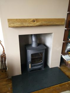 Charnwood C4 in gun metal grey fitted on a lovely riven slate hearth & with a oak mantle beam all supplied by us.