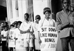 "Demonstration at the Greyhound Bus station in Stuttgart, Arkansas, showing a woman holding a sign that reads: ""Sit Down Like Human Beings"". SNCC Arkansas Project. 1965"